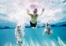 Young boy and two young girls jumping into swimming pool underwater view