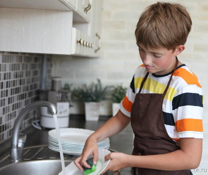 Мальчик моет посуду