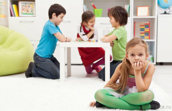 Девочка сидит вдали от других детей