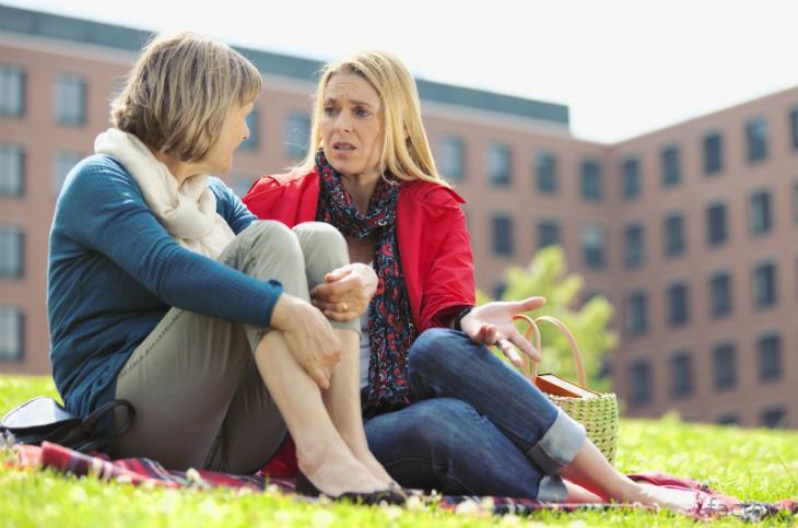 Две женщины разговаривают на траве