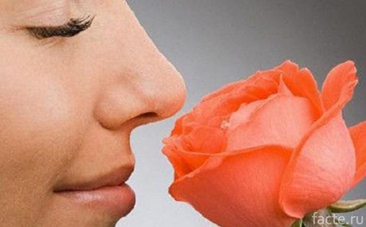 Женщина нюхает розу